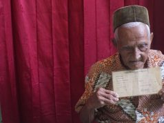 Nyak Sandang menunjukkan surat obligasi yang diberikan saat menyumbangkan hartanya untuk pembelian pesawat Seulawah 001 atau saat ini bernama Garuda Indonesia, di kediamannya, Selasa (6/3). (Waspada/Dani Randi)