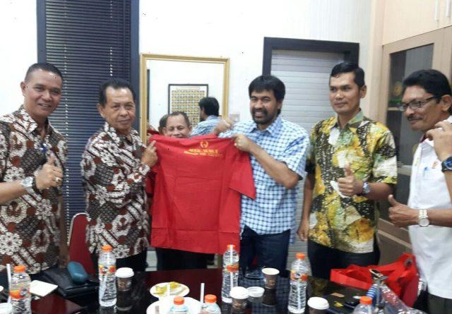Ketum KONI Aceh Muzakir Manaf menyerahkan baju merah bertuliskan Aceh Teugah-Sumut Paten, tuan rumah PON 2024, kepada Ketum KONI Jogjakarta, Triyandi Mulkan di KONI Aceh, Kamis (17/4/2018). (Foto/Aldin NL)