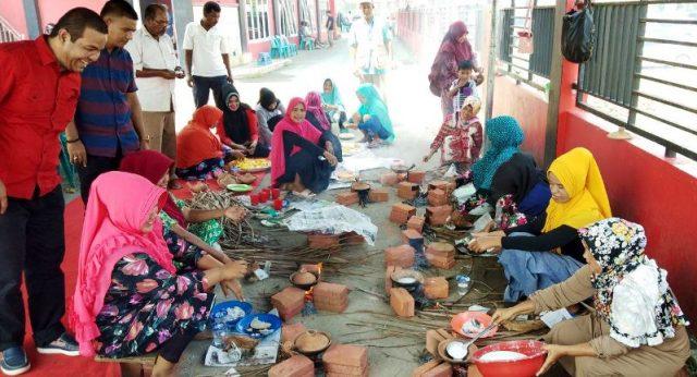 Sekretaris DPW Partai Aceh, Kabupaten Pidie Tgk.Anwar Husen, (baju merah-red) sedang melihat para kaum ibu memasak apam di halaman belakang kantor DPW PA, Pidie. Kamis (12/4/2018). (Foto/Muhammad Riza)
