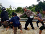 Salah seorang petugas Polisi Lalulintas tampak sedang membantu pengendara yang melintasi banjir di jalan raya, Selasa hari ini (24/4/2018). (Foto/Arief H)