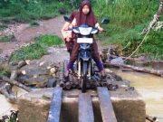 Dua murid SD hendak menyeberang dengan sepeda motor melintasi jembatan darurat di Dusun Alue Meuh, Desa Gunci, Kec. Sawang, Aceh Utara. (Foto/Ist)