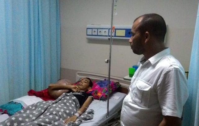Ketua PMI Kota Lhokseumawe Junaidi Yahya saat menjenguk Hendrizki,19, warga Seunudon, Aceh Utara, di Rumah Sakit Umum Zainal Abidin, Banda Aceh. (Foto/Ist)