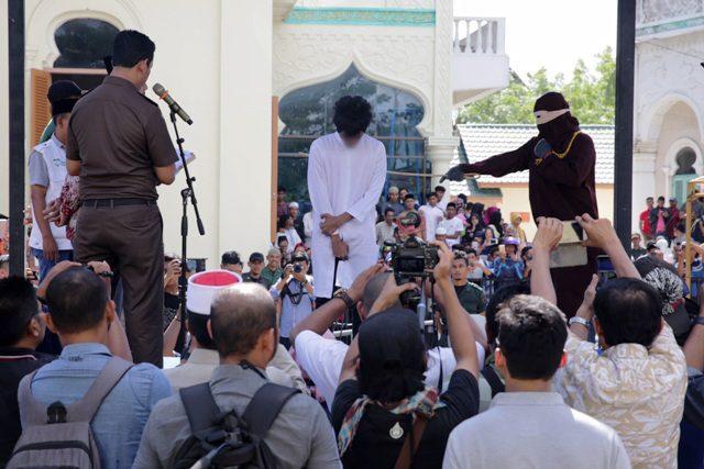 Pelanggar Syariat Islam kena hukuman cambuk di Masjid Raya Uleu Lheue, Banda Aceh, Jumat (13/7/2018). (Foto/Humas)