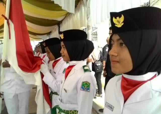 Petugas pengibar bendera (Paskibra) Aceh Jaya mencium bendera merah putih saat pengukuhan di pendopo bupati setempat di Calang, Kamis sore (16/8/2018). (Foto/Dedi Iskandar).