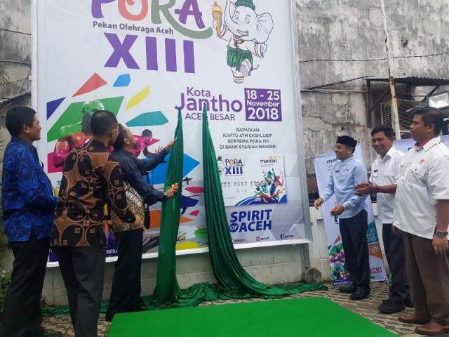 Ketua Umum Panitia PORA XIII Aceh Besar, Iskandar dan Manager Area BSM Aceh, Ismul Fahri, membuka selubung billboad PORA di kantor BSM Aceh di Banda Aceh, Rabu (19/9/2018). (Foto/Ist)