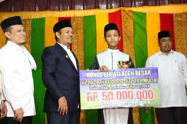 Bupati Aceh Besar Ir Mawardi Ali menyerahkan hadiah Rp50 juta juara Hafidz 30 juz termuda Aceh Besar, Muhammad Safwan,19, pada peringatan tahun baru Islam 1 Muharram 1440 H di Masjid Jamik Abu Indrapuri, Senin malam (10/9/2018). (Foto/Ist)
