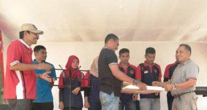 Ketua Harian KONI Aceh, Kamaruddin Abubakar alias Abu Razak, menyerahkan hadiah hasil lucky draw bagi atlet binaan KONI Aceh yang beruntung, di pantai Leupung, Aceh Besar, Minggu (21/10/2018). (Foto/Nazar)