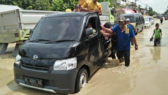 Sejumlah warga Samudera, Aceh Utara, sedang mendorong mobil warga yang mogok saat melintasi banjir di Jalan Lintas Sumatera (Jalinsum), Sabtu (17/11/2018). (Foto/Zainal Abidin)