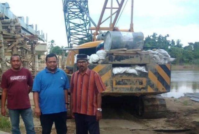 Asrizal Asnawi (kaos biru), anggota DPRA saat meninjau pembangunan lantai jembatan penghubung Kecamatan Seruway – Kecamatan Bendahara, Aceh Tamiang. (Foto/Ist)