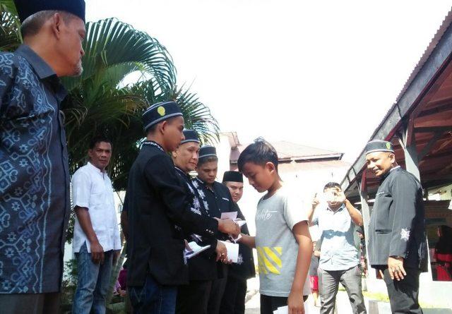 Kalapas Klas II A Kota Lhokseumawe Nawawi menyaksikan napi kasus narkoba Wan dan Fad sedang membagikan amplop untuk menyantuni anak yatim pada acara Maulid Nabi di Lapas setempat, Sabtu (15/12/2018). (Foto/Zainuddin Abdullah)