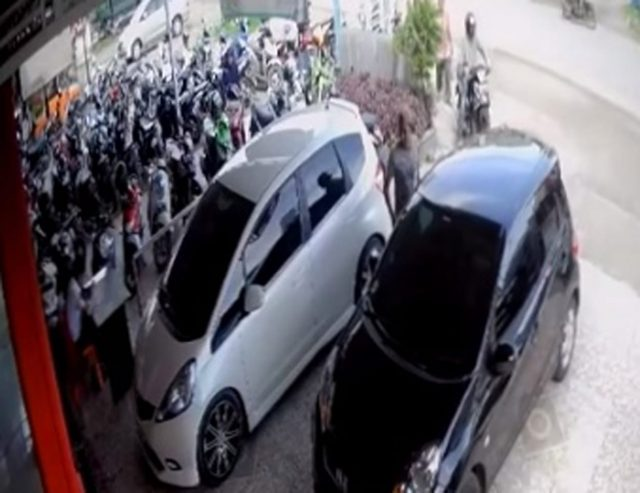 Dua orang pelaku pencuri uang Rp170 juta dalam mobil Honda warna hitam milik dr Suryadi, satu orang pelaku tampak berdiri di samping mobil dan satunya lagi menunggu di atas sepeda motor terekam CCTV RSU Ibnu Sina, Sigli. (Foto/Muhammad Riza)