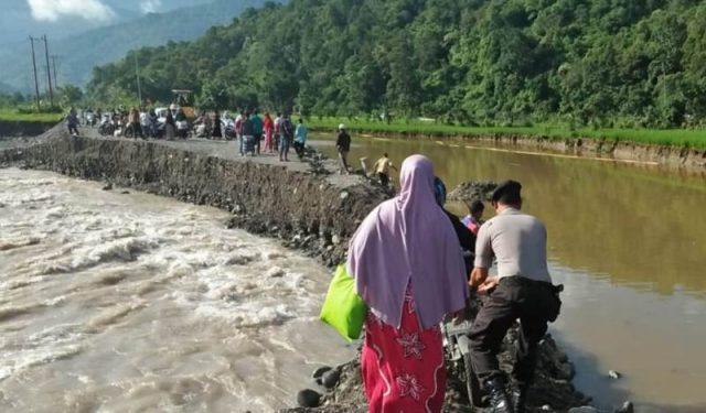 Tampak petugas sedang membantu warga yang akan melintas jalan lintas Beureunuen-Meulaboh di kawasan Gampong Blang Bungong dan Blang Jeurat, yang kembali putus akibat diterjang air luapan sungai, Sabtu (1/12/2018). (Foto/Muhammad Riza)