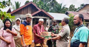 Bupati Aceh Barat, H Ramli MS, menyalurkan bantuan masa panik kepada korban banjir di Desa Napai, Kecamatan Woyla Barat, Minggu sore (2/12/2018). (Foto/Dedi Iskandar)