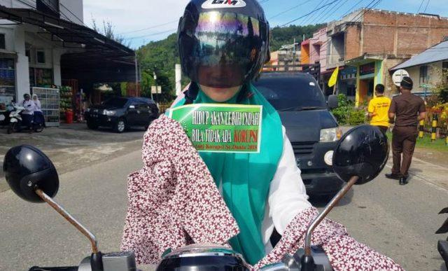 Seorang wanita berkenderaan memegang stiker anti korupsi, sementara tampak di pinggir jalan para pegawai Kejaksaan Aceh Selatan membagikan kaos dan stiker Anti Korupsi kepada pengguna jalan lainnya, di Simpang Kedai Haru, Tapaktuan, Aceh Selatan, Senin (10/12/2018). (Foto/Faisal).