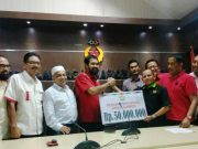 Ketum KONI Aceh Muzakir Manaf menyerahkan bonus secara simbolis, diterima T.Rayuan Sukma mewakili lifter peraih perunggu Asian Games, Surahmat, di KONI Aceh, Kamis (20/12/2018). (Foto/Aldin NL)