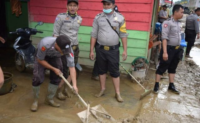 Terlihat pada Kamis (3/1/2019), anggota Polri membersihkan lokasi terparah yang diterjang banjir, di Kutacane. (Foto/abadi selian)