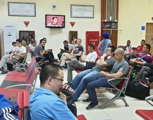 Para TKA asal Cina yang kedapatan bekerja di Aceh tanpa dokumen lengkap,tampak sedang menunggu boarding di Bandara Sultan Iskandar Muda, Blang Bintang, Aceh Besar, Jumat sore (19/1/2019). (Foto/Ist)