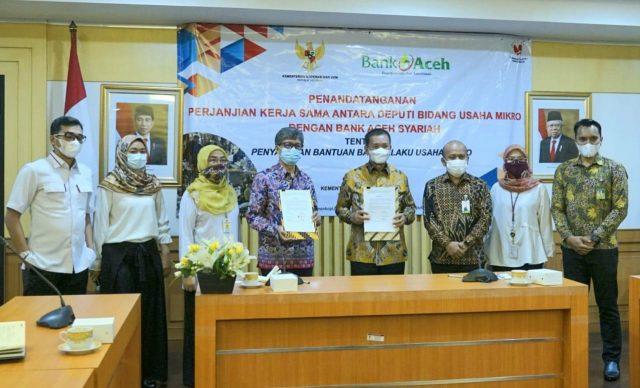 irektur Utama Bank Aceh Syariah, Haizir Sulaiman, didampingi Pemimpin Divisi Treasury Dana & Jasa, Erwin Konadi, usai menandatangani kerjasama penyaluran Bantuan bagi Pelaku Usaha Mikro (BPUM) di kantor Kementerian Koperasi dan UKM di Jakarta, Selasa (6/4/2021). (Foto/Ist)
